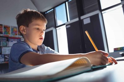 Boy writing on book at desk in classroom